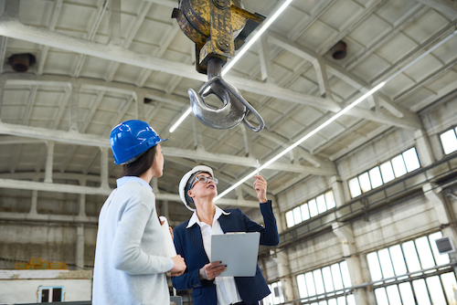 two women in a warehouse looking at a construction crane