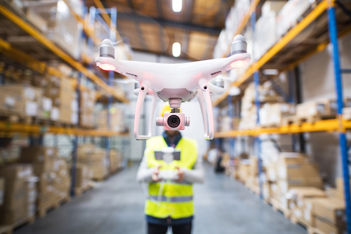 warehouse with a man flying a drone in it
