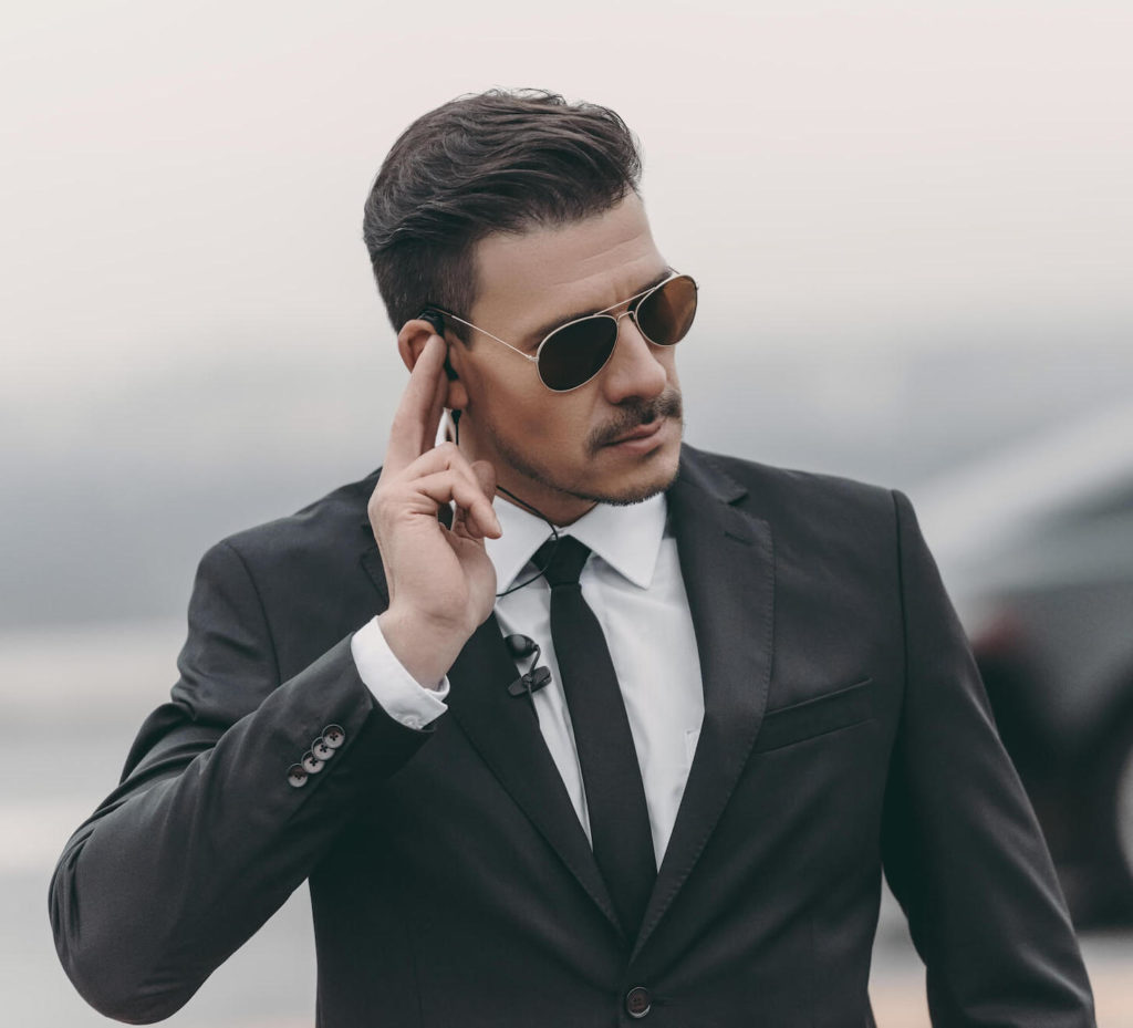 Canva - handsome bodyguard listening message with security earpiece (1)