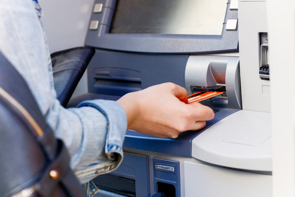 woman-putting-card-into-atm-at-bank